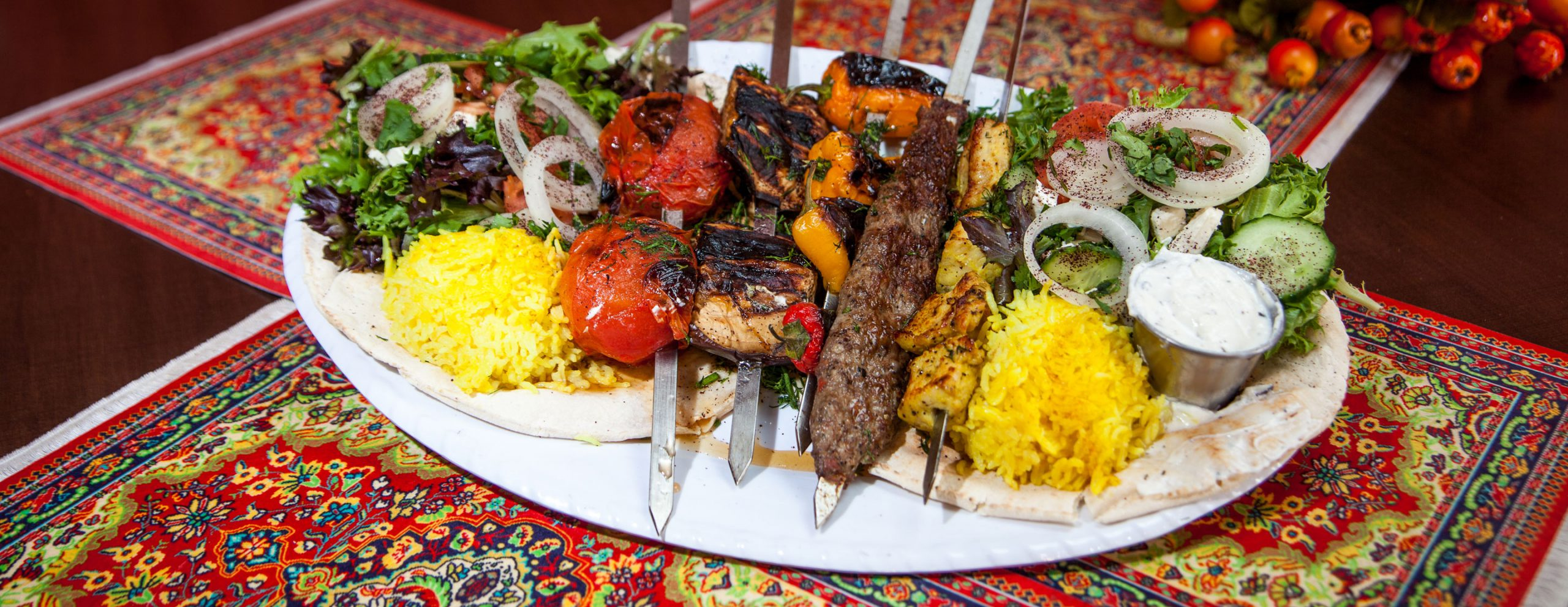A platter of Caspian Grill food including kabobs, rice, salad, and pita.
