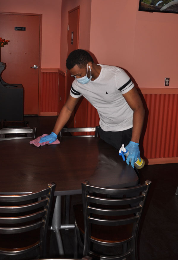 A worker sanitizing tables at the Caspian Grill restaurant dining space